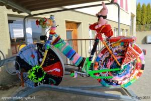 Un vélo entièrement décoré de laine sous le préau d'une école